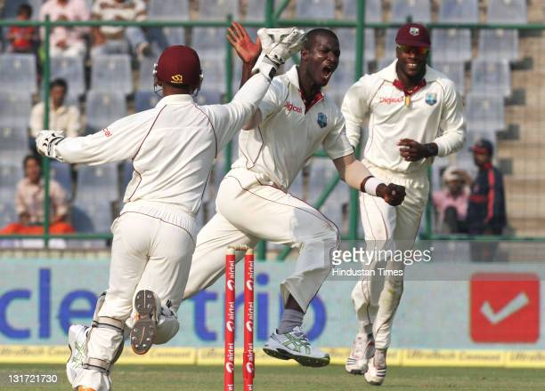 West Indies bowler Darren Sammy celebrates after taking the wicket of Indian captain Mahendra Singh Dhoni during the second day of the first Test...