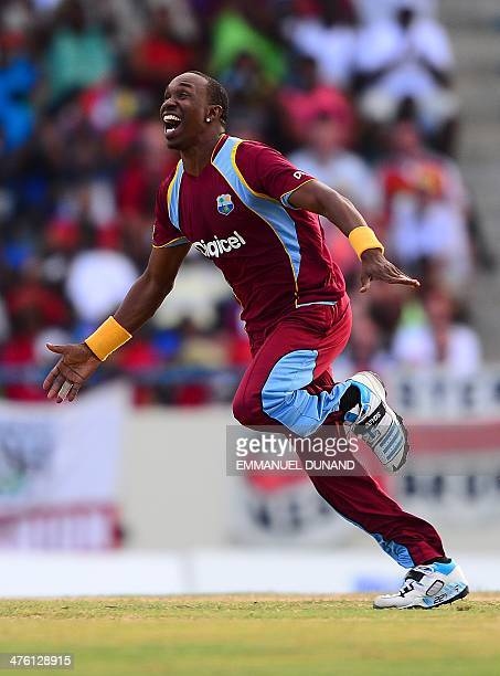 West Indies bowler Dwayne Bravo celebrates after taking the wicket of England's batsman Joe Root during the second One Day International match...