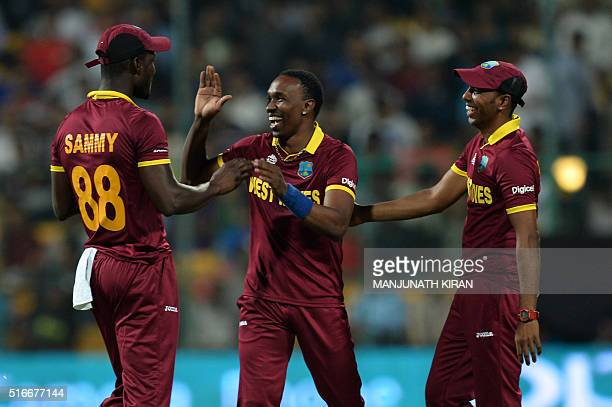 West Indies bowler Dwayne Bravo celebrates the wicket of Sri Lankan batsman Angelo Mathews with team captain Darren Sammy during the World T20...