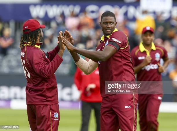West Indies bowler Jason Holder celebrates with West Indies' Chris Gayle after taking the wicket of England captain Eoin Morgan during the third one...