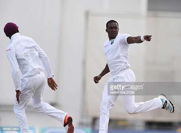 West Indies bowler Jerome Taylor celebrates after taking the second innings wicket of English Captain Alastair Cook for 13 on day three of the first...