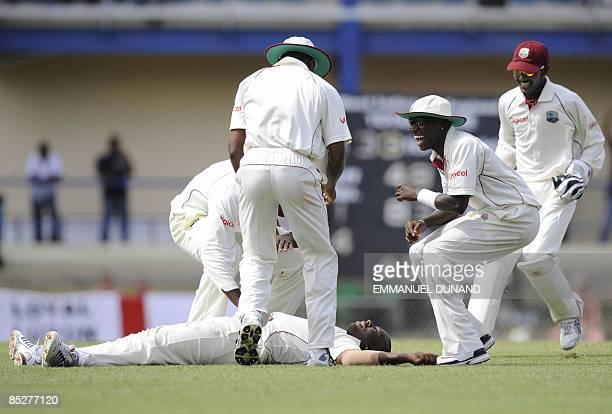 West Indies bowler Ryan Hinds celebrates with teammates after taking the wicket of English batsman Kevin Pietersen, during the first day of the last...