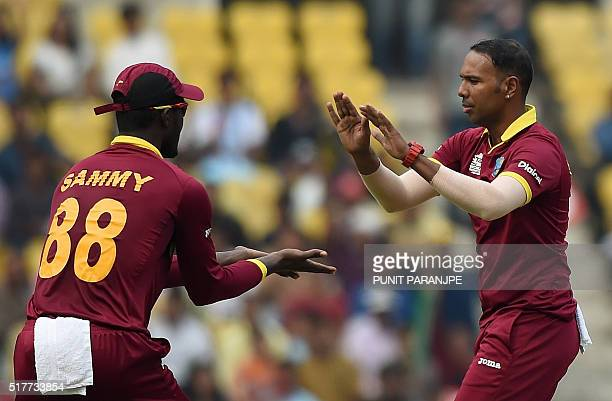 West Indies bowler Samuel Badreecelebrates with captain Darren Sammy after taking the wicket of unseen Afghanistan batsman Usman Ghani during the...