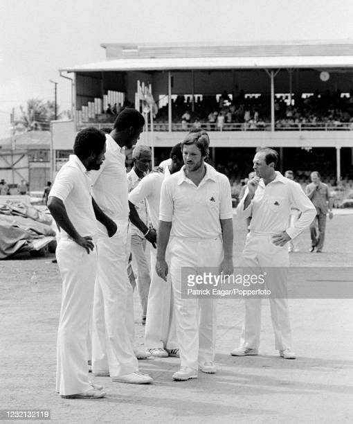 West Indies bowlers Andy Roberts and Joel Garner , with Ian Botham and Geoffrey Boycott of England, inspect the damaged wicket before the 1st Test...