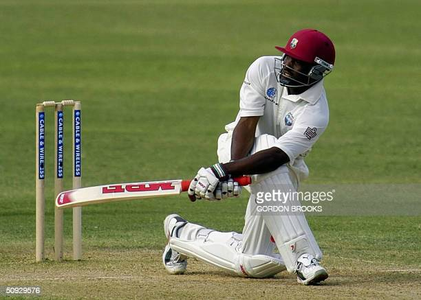 West Indies' captain Brian Lara sweeps Bangladesh spin bowler Mushfiqur Rahman for 4 during his century on the second day on the second Cable &...