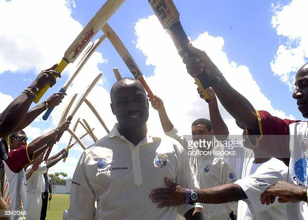 West Indies captain Brian Lara walks under an arch of bats 12 April, 2004 as teammates congratulate him on his record breaking 385 on the third day...