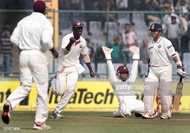 West Indies captain Darren Sammy and wicketkeeper Carlton Baugh celebrate after taking the wicket of Sachin Tendulkar during the fourth day of the...