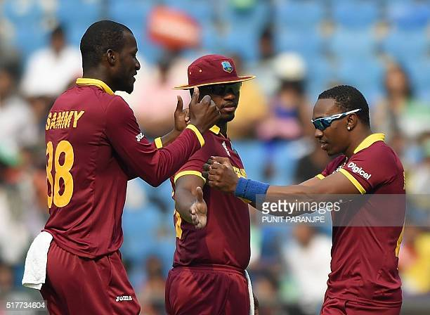 West Indies captain Darren Sammy celebrates with teammate Dwayne Bravoafter taking the wicket of Afghanistan batsman Gulbadin Naib during the World...