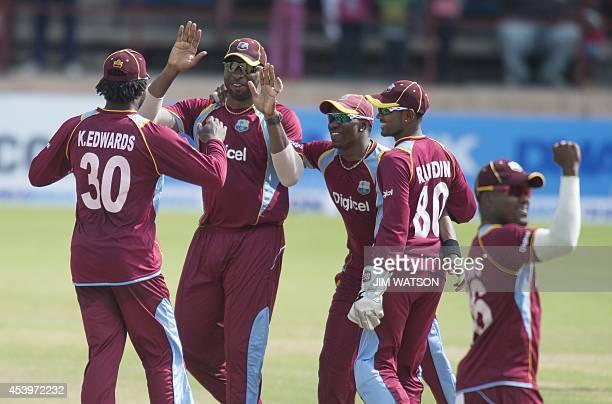 West Indies captain Dwayne Bravo celebrates with teammates Kirk Edwards Kieron Pollard Denesh Ramdin and Darren Bravo their victory by 177 runs over...
