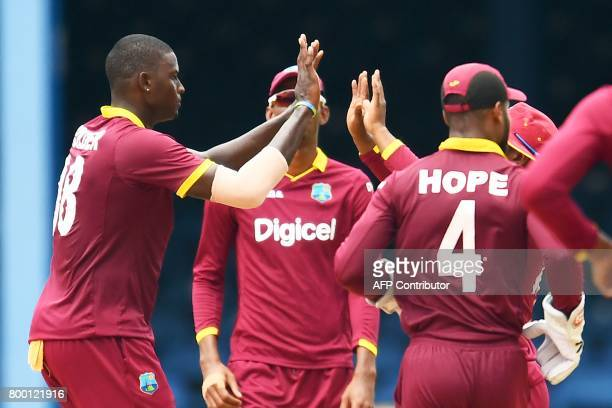 West Indies' captain Jason Holder celebrates with teammates after dismissing India's Yuvraj Singh during the first One Day International match...