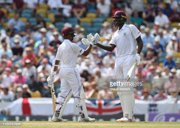 West Indies captain Jason Holder congratulates Shane Dowrich of West Indies on reaching 50 during Day Three of the First Test match between England...