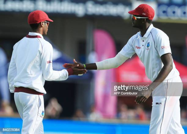 West Indies' captain Jason Holder congratulates West Indies' Kraigg Brathwaite for making the catch and taking England's Moeen Ali wicket for 84 on...