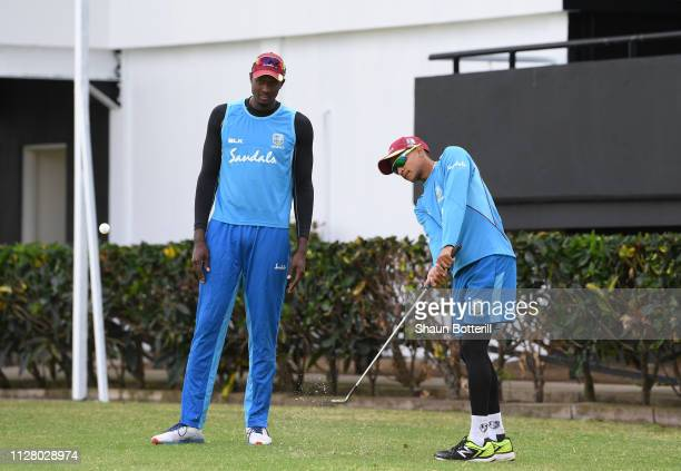 West Indies captain Jason Holder helps team-mate Shane Dowrich with his golf swing during a net session at Darren Sammy National Cricket Stadium on...