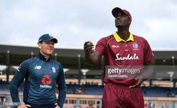West Indies captain Jason Holder tosses the coin alongside England captain Eoin Morgan ahead of the 3rd One Day International match between the West...