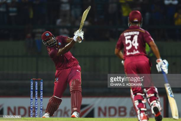 West Indies' captain Kieron Pollard plays a shot as his teammate Lendl Simmons watches during the first Twenty20 international cricket match of a...