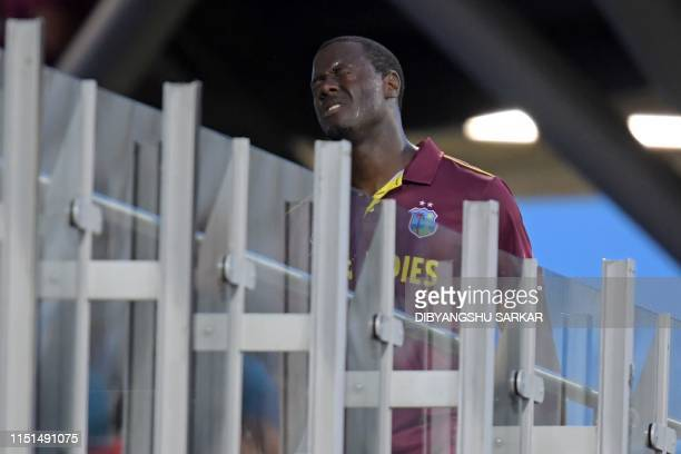 West Indies' Carlos Brathwaite reacts as he returns to the dressing room having fallen short in the runchase during the 2019 Cricket World Cup group...