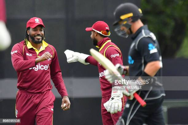 West Indies Chris Gayle celebrates taking the catch of New Zealand's Neil Broom with teammate keeper Shai Hope during the third one day international...