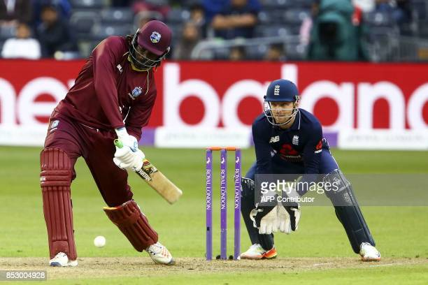 West Indies' Chris Gayle plays a shot as England's Jos Buttler keeps wicket during the third one day international cricket match played between...