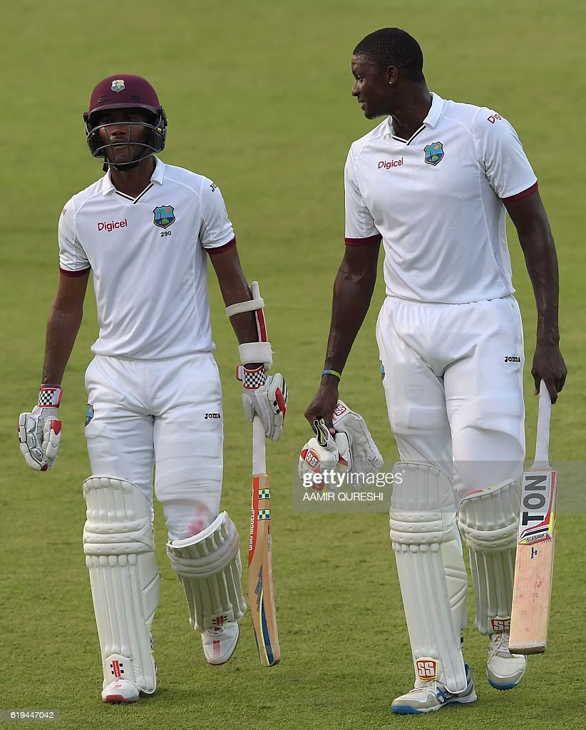 West Indies' cricket captain Jason Holder (R) and teammate Kraigg Brathwaite walk back to pavilion at the end of the second day of the third and final Test between Pakistan and the West Indies at the Sharjah Cricket Stadium in Sharjah on October 31, 2016. Pakistan, resuming at 255-8, were dismissed for 281 in their first innings on the second day of the third and final Test against West Indies in Sharjah. / AFP / AAMIR