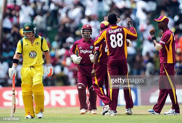 West Indies cricket team captain Darren Sammy celebrates with teammates after dismissing Australian batsman David Warner during the third-of-five One...