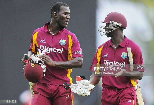 West Indies cricket team captain Darren Sammy talks with teammate Kemar Roach as they leave the field after being run out during the third-of-five...