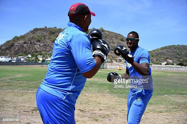 West Indies cricket team captain Jason Holder and coach Phil Simmons playfully box to pay their respect to late boxer Muhammad Ali during a practice...
