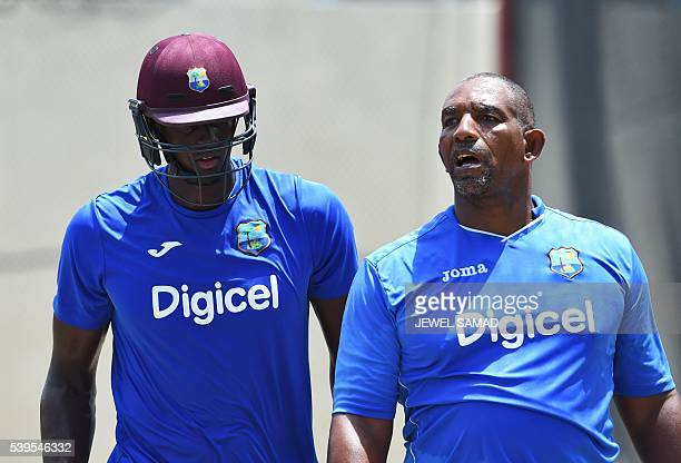 West Indies cricket team captain Jason Holder listens to his team coach Phil Simmons during a practice session at the Warner Park stadium in...