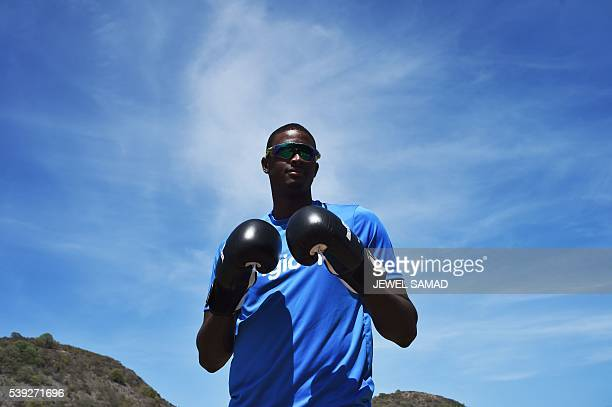 West Indies cricket team captain Jason Holder poses wearing a pair of boxing gloves to pay his respect to late boxer Muhammad Ali during a practice...