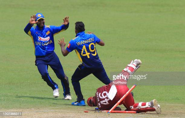 West Indies cricketer Darren Bravo crashes in to the stumps as he is run out while Sri Lankan cricketer Wanidu Hasaranga celebrates with Sri Lankan...