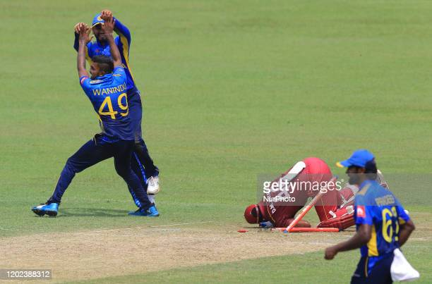 West Indies cricketer Darren Bravo crashes in to the stumps as he is run out while Sri Lankan cricketer Wanidu Hasaranga celebrates during the 1st...