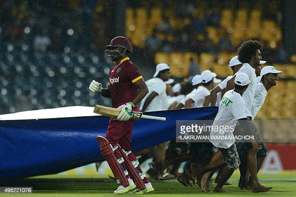 West Indies cricketer Darren Bravo runs as Sri Lankan ground staff cover the pitch as rain stopped play during the first One Day International match...