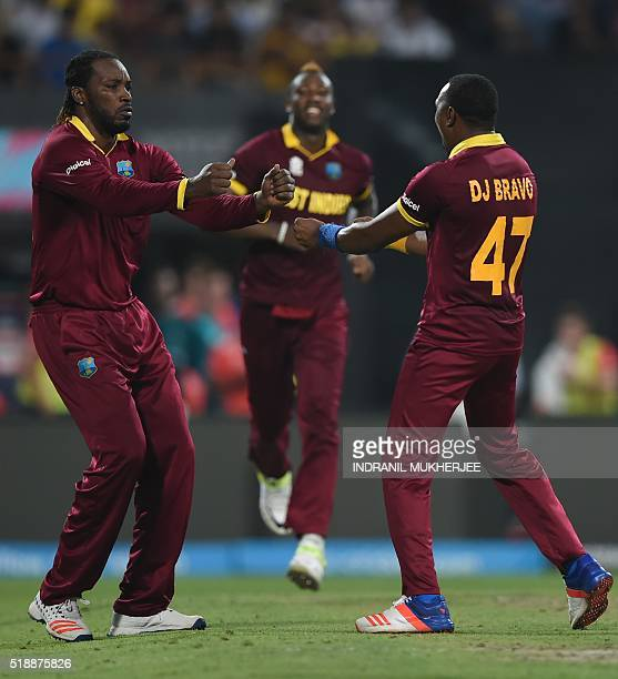 West Indies cricketer Dwayne Bravocelebrates with teammate Chris Gayle after the dismissal of England's Joe Root during the World T20 cricket...