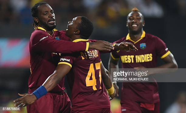 West Indies cricketer Dwayne Bravocelebrates with teammate Chris Gayle after the dismissal of England's Ben Stokes during the World T20 cricket...