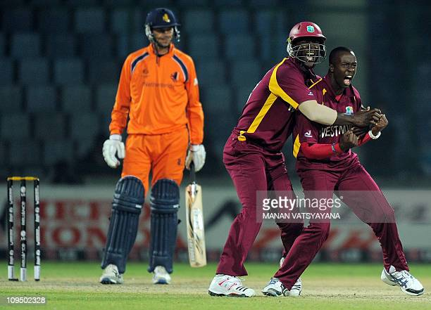 West Indies cricketer Kemar Roach celebrates with captain Darren Sammy after taking the wicket of Netherlands cricketer Bernard Loots during their...