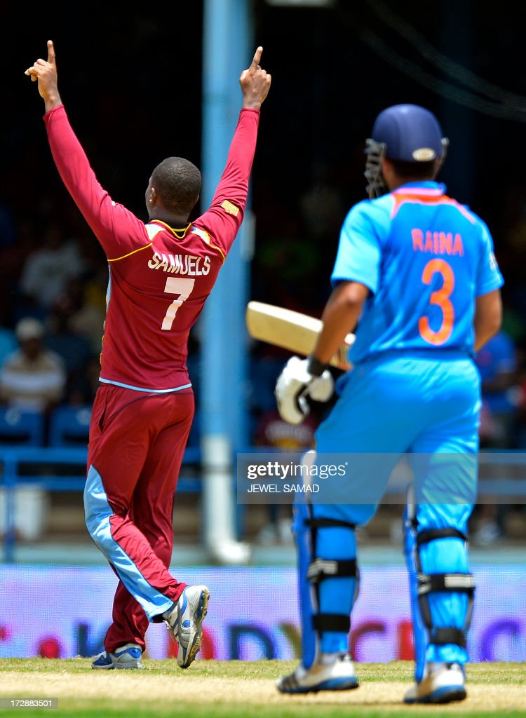 West Indies cricketer Marlon Samuels (L) celebrates dismissing Indian batsman Suresh Raina during the fourth match of the Tri-Nation series between India and West Indies at the Queen's Park Oval in Port of Spain on July 5, 2013. West Indies won the toss and elected to field. AFP PHOTO/Jewel Samad
