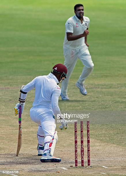 West Indies' cricketer Marlon Samuels looks down as India's cricketer Ravichandran Ashwin runs to teammates during day four of the cricket test match...