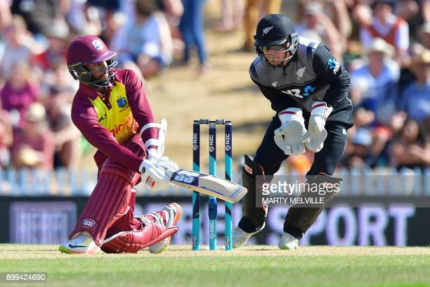 West Indies cricketer Shai Hope bats as New Zealand's wicketkeeper Glenn Phillips looks on during the first Twenty20 international cricket match...