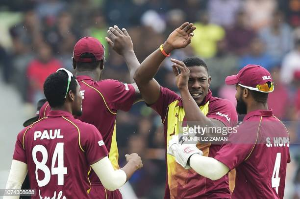 West Indies cricketer Sheldon Cottrell celebrates with his teammates after the dismissal of the Bangladeshi cricketer Tamim Iqbal during the first...