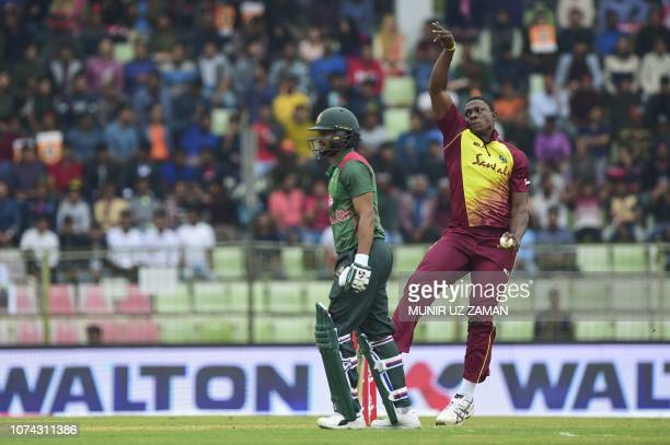 West Indies cricketer Sheldon Cottrell delivers a ball as the Bangladesh cricket captain Shakib Al Hasan looks on during the first Twenty20 cricket...