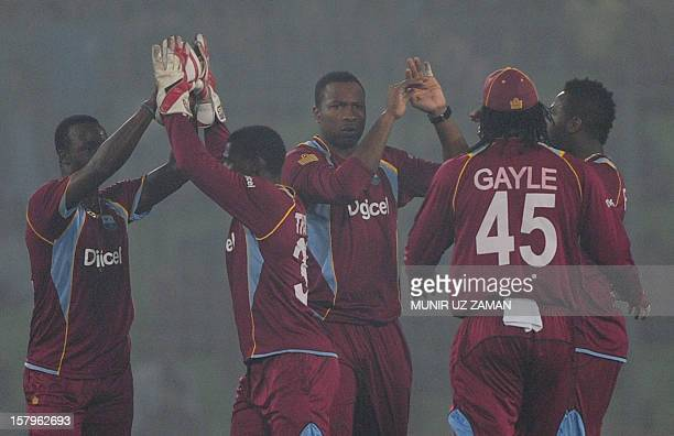 West Indies cricketers celebrate after the dismissal of the unseen Bangladeshi batsman Anamul Haque during the fifth one day international between...