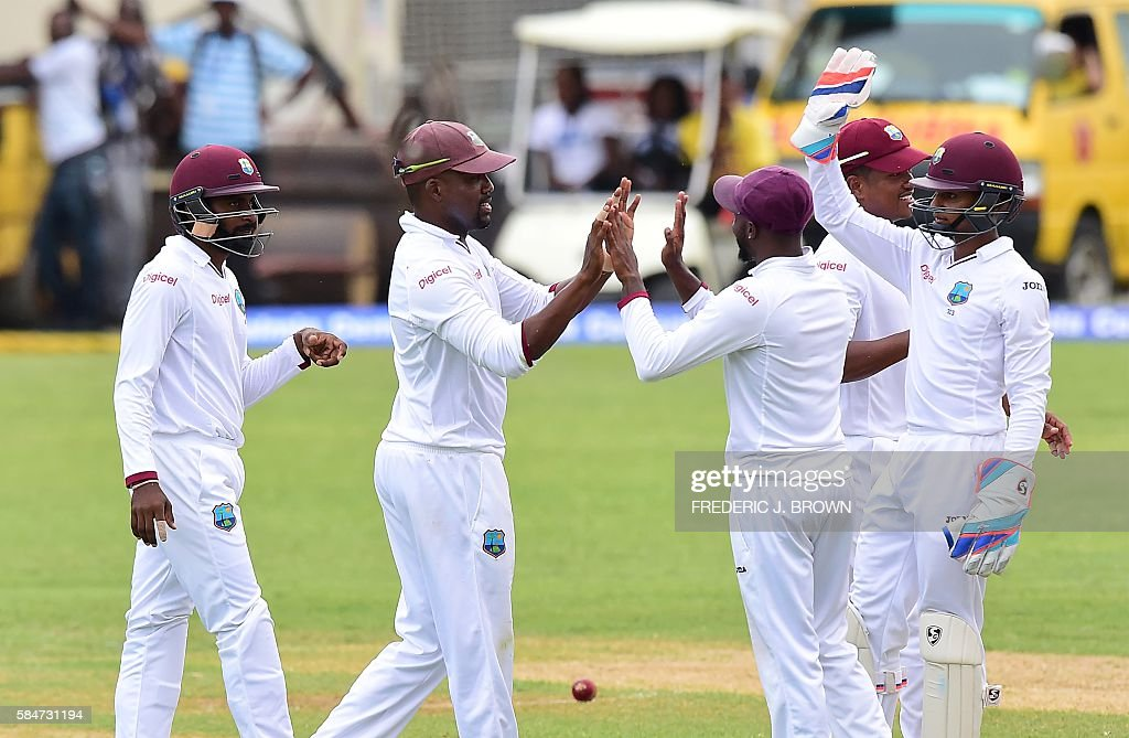 West Indies Darren Bravo (2/L) celebrates with teammates after catching out India's Shikhar Dhawan on July 30, 2016 in Kingston, Jamaica on the first day of the 2nd Test between India and the West Indies. / AFP / Frederic J. BROWN