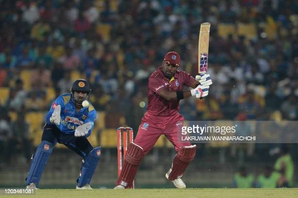 West Indies Darren Bravo is watched by Sri Lankan wicketkeeper Kusal Janith Perera as he plays a shot during the second one day international cricket...