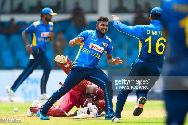 West Indies' Darren Bravo loses his balance and crashes into the wicket after being runned out by Sri Lanka's Wanidu Hasaranga as he celebrates with...