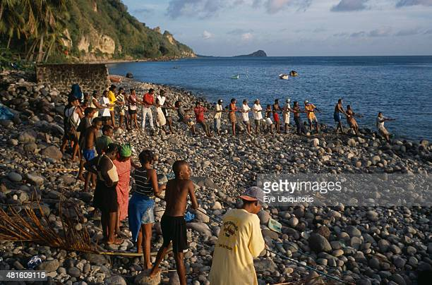 West Indies Dominica Pointe Michel Villagers on beach pulling a seine net as fishermen attempt to catch tuna close to shore