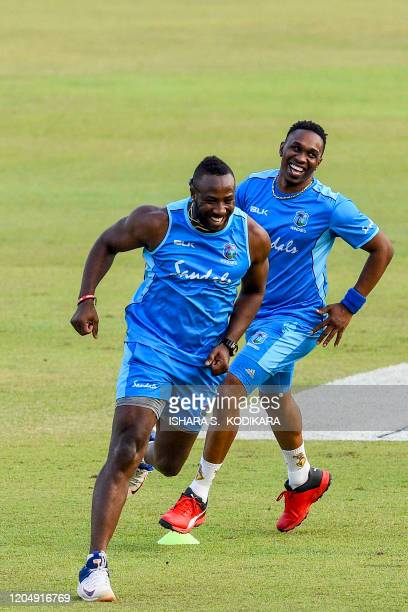 West Indies' Dwayne Bravo and teammate Andre Russell attend a practice session at the Pallekele International Cricket Stadium in Kandy on March 3...