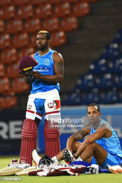 West Indies' Fabian Allen and Lendl Simmons take a break during a practice session at the Pallekele International Cricket Stadium in Kandy on March 3...