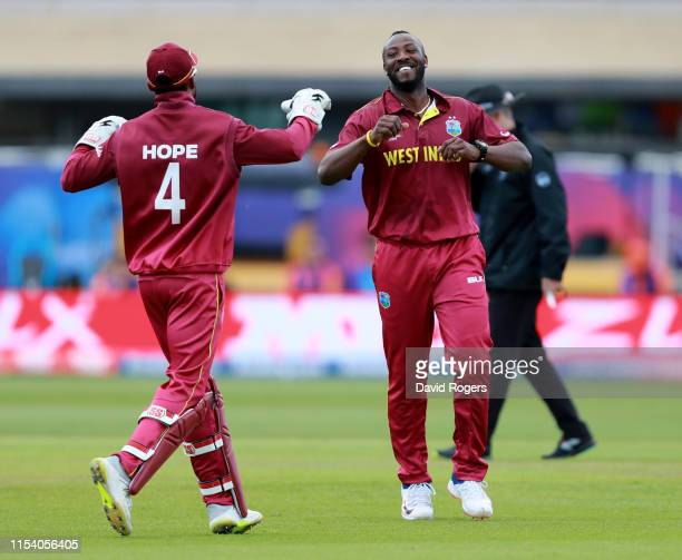 West Indies fast bowler Andre Russell celebrates with wicketkeeper Shai Hope after they combine to take the wicket of Alex Carey during the Group...