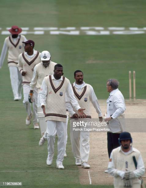 West Indies fast bowlers Curtly Ambrose and Kenny Benjamin talk to umpire Dickie Bird as the teams leave the field at the end of England's 1st...
