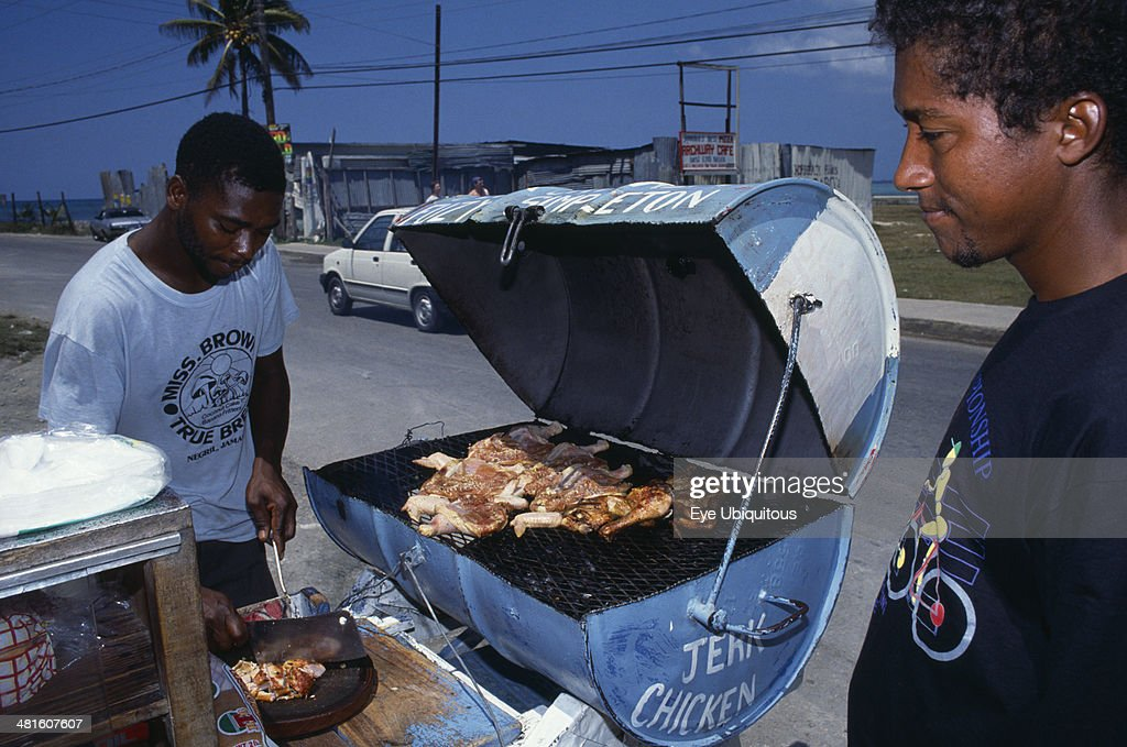 West Indies, Jamaica, Market, Man cooking jerk chicken on roadside stall with waiting customer.