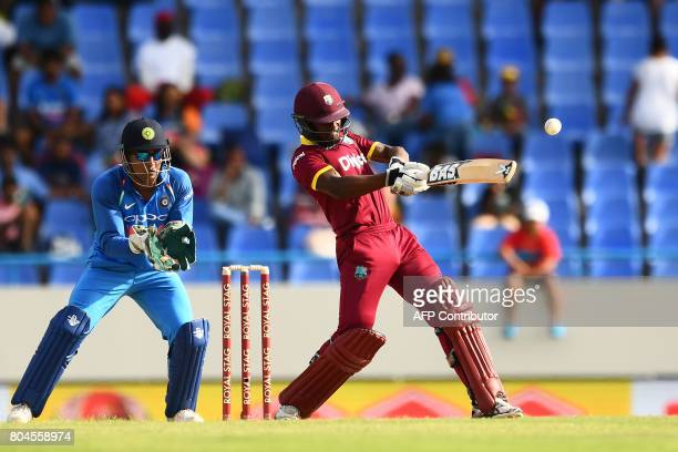 West Indies' Jason Mohammed plays shot as India's wicketkeeper MS Dhoni looks on during the third One Day International match between West Indies and...